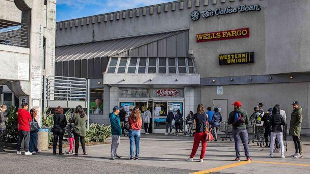 PHOTO: People wait in line to buy food at a grocery store in Los Angeles, March 21, 2020. (Apu Gomes/AFP/Getty Images)