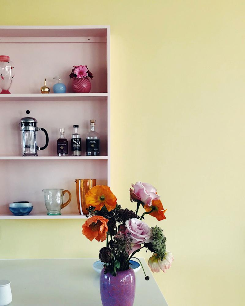 """Store the functional, spotlight the pretty: The trick to keeping your kitchen cool, not cluttered? Take a cue from Marie Kondo and only give public real estate to the pieces that bring you joy. """"I built this open shelf specifically for this wall to display some nicer things,"""" Lisbeth says. """"It's a really quick and easy way to add personality."""" A designated spot also allows extra breathing room elsewhere in the space, reducing any sense of visual clutter."""
