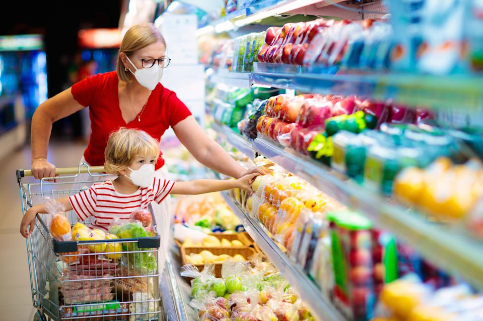 Shopping with kids during virus outbreak. Mother and child wearing surgical face mask buying fruit in supermarket. Mom and little boy buy fresh vegetable in grocery store. Family in shop.