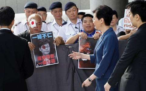 Hong Kong's Chief Executive Carrie Lam walks past protesters outside her office  - Credit: Reuters