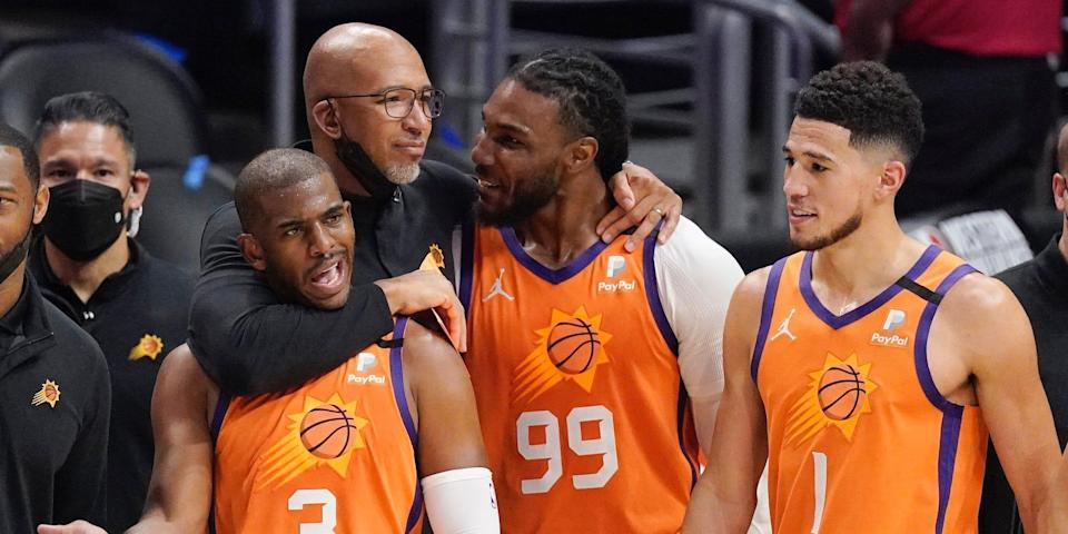 Monty Williams puts his arms around Chris Paul, Jae Crowder, and Devin Booker.