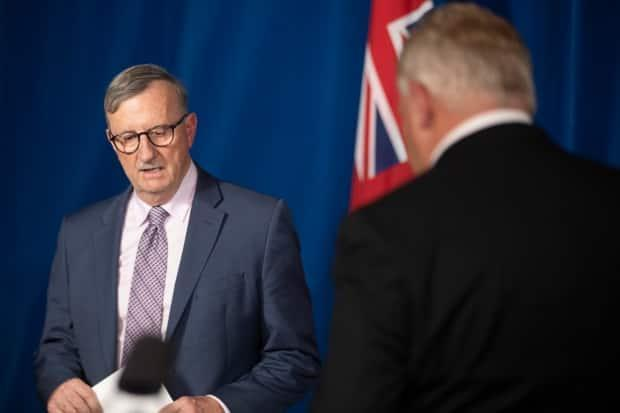 Dr. David Williams, Ontario's chief medical officer, and Premier Doug Ford trade places at the podium during a news conference at the Ontario legislature in Toronto on Nov. 25, 2020.