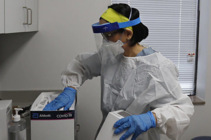 """In this Friday, April 24, 2020 photo, Wayne State University medical school student Lucia Luna-Wong checks COVID-19 test kits at a testing center in Detroit. Luna-Wong said she didn't hesitate when offered a chance to join what she calls a """"crash course in public health."""" She wants to specialize in infectious diseases. She's volunteering in one of America's hardest-hit cities, testing police officers, firefighters, bus drivers and other essential workers who keep Detroit running. (AP Photo/Carlos Osorio)"""