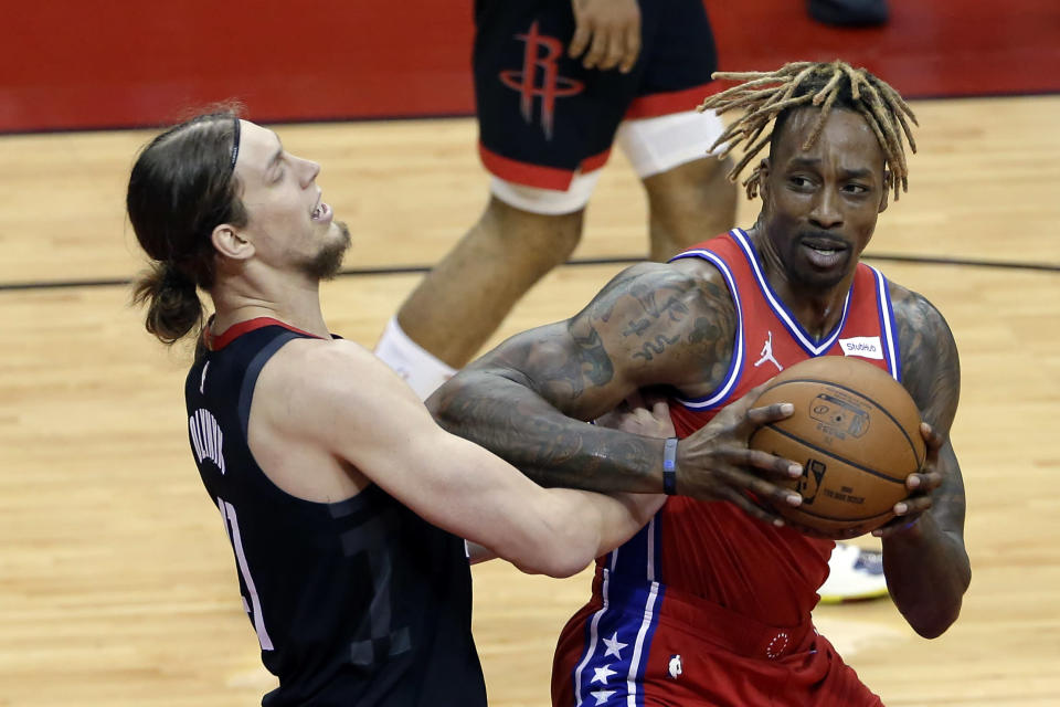 Houston Rockets forward Kelly Olynyk, left, takes an elbow from Philadelphia 76ers center Dwight Howard, right, as he looks for a shot during the first half of an NBA basketball game Wednesday, May 5, 2021, in Houston. (AP Photo/Michael Wyke, Pool)