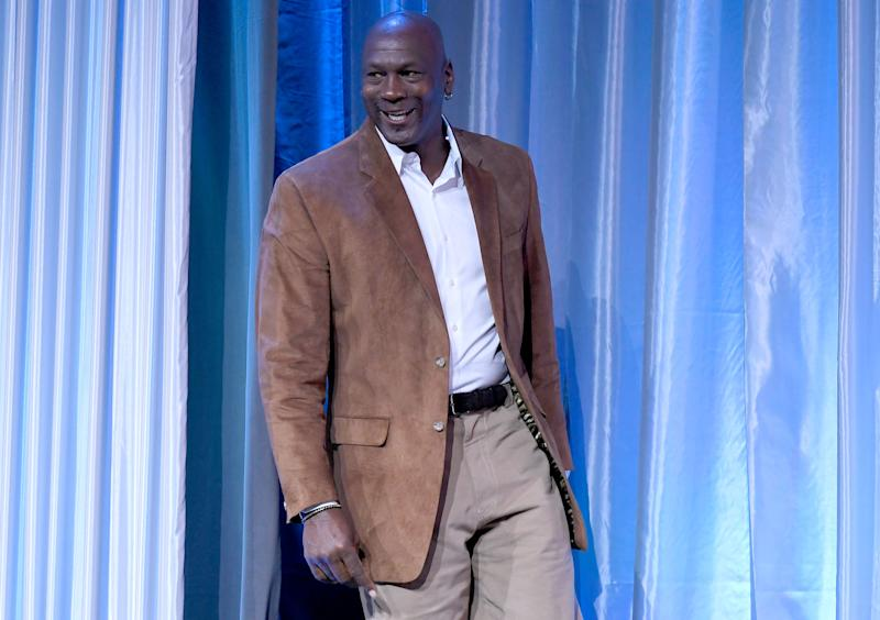 Michael Jordan looks stunning in brown leather suit and light brown pant to match.