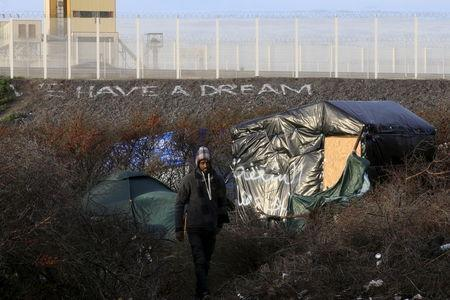 "A migrant walks between makeshift shelters near an embankment with the message, ""We Have A Dream"" below a fence topped with razor wire in the ""new jungle"", a field where migrants and asylum seekers gather in Calais, France, in this December 30, 2015 file photo. REUTERS/Pascal Rossignol/Files"