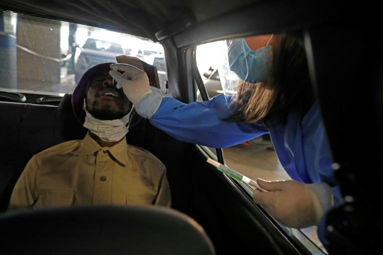 Testing time: A health worker collects a nasal swab at a drive-through site in Centurion, South Africa