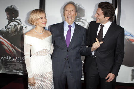 """Actress Sienna Miller (L), director Clint Eastwood and actor Bradley Cooper ( R) arrive for the premiere of the film """"American Sniper"""" in New York, December 15, 2014.  REUTERS/Carlo Allegri"""