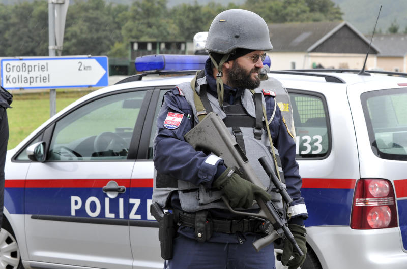 Police stand near the villages of Grosspriel and Kollapriel some 90 kilometers (55 miles) west of Vienna, Austria, Tuesday, Sept. 17, 2013, where a man is barricading himself inside a farm building. Police say a man shot and killed two police officers and the driver of an emergency rescue vehicle in central Austria, the dpa news agency reports. The news agency reported that a police SWAT team was on the scene after the overnight attack in Annaberg, about 115 kilometers (70 miles) southwest of Vienna. Austria's interior ministry said the three were shot without going into details. (AP Photo/Hans Punz)