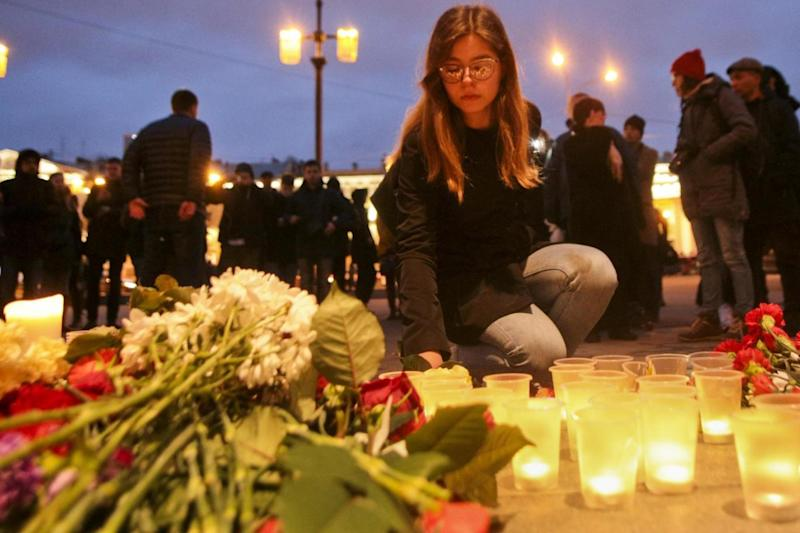 Tributes: A woman lights a candle at an entrance to Sennaya subway station (AP)