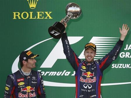 Red Bull Formula One driver Sebastian Vettel (R) of Germany celebrates with his trophy after winning the Japanese F1 Grand Prix at the Suzuka circuit October 13, 2013. REUTERS/Toru Hanai