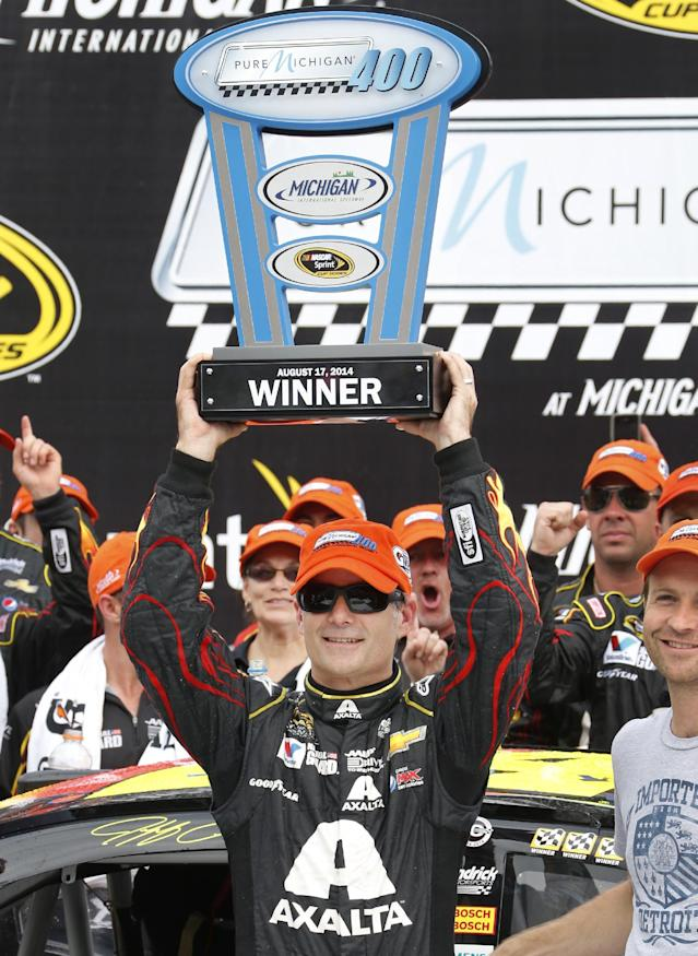 Jeff Gordon celebrates his victory holding up the trophy after the NASCAR Sprint Cup Series Pure Michigan 400 auto race at Michigan International Speedway in Brooklyn, Mich., Sunday, Aug. 17, 2014. (AP Photo/Bob Brodbeck)