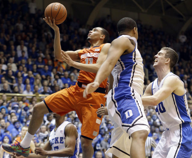 Syracuse's Tyler Ennis (11) drives to the basket against Duke's Marshall Plumlee, right, and Andre Dawkins during the first half of an NCAA college basketball game in Durham, N.C., Saturday, Feb. 22, 2014. (AP Photo/Gerry Broome)