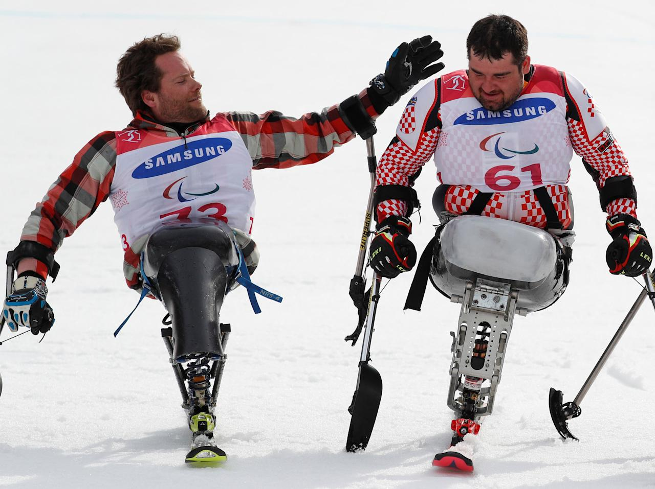 Alpine Skiing - Pyeongchang 2018 Winter Paralympics - Men's Slalom - Sitting - Final - Jeongseon Alpine Centre - Jeongseon, South Korea - March 17, 2018 - Silver medallist Tyler Walker (73) of the U.S. pats gold medallist Dino Sokolovic (61) of Croatia on the back. REUTERS/Paul Hanna