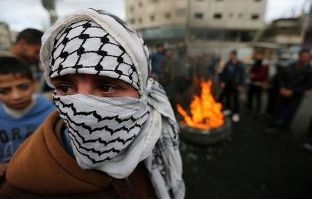 A masked Palestinian takes part in a protest against U.S. President Donald Trump's decision to recognize Jerusalem as the capital of Israel, in Khan Younis in the southern Gaza Strip
