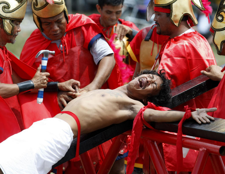 Volunteers dressed as Roman centurions drive nails through the palms of a Catholic devotee in a reenactment of the crucifixion of Jesus Christ on Good Friday at San Pedro Cutud, Pampanga province, north of Manila, Philippines, Friday, April 6, 2012. More than two dozen Catholic devotees have themselves nailed on the cross on Good Friday, a practice that has become a tourist attraction but is rejected by the Catholic Church. (AP Photo/Bullit Marquez)