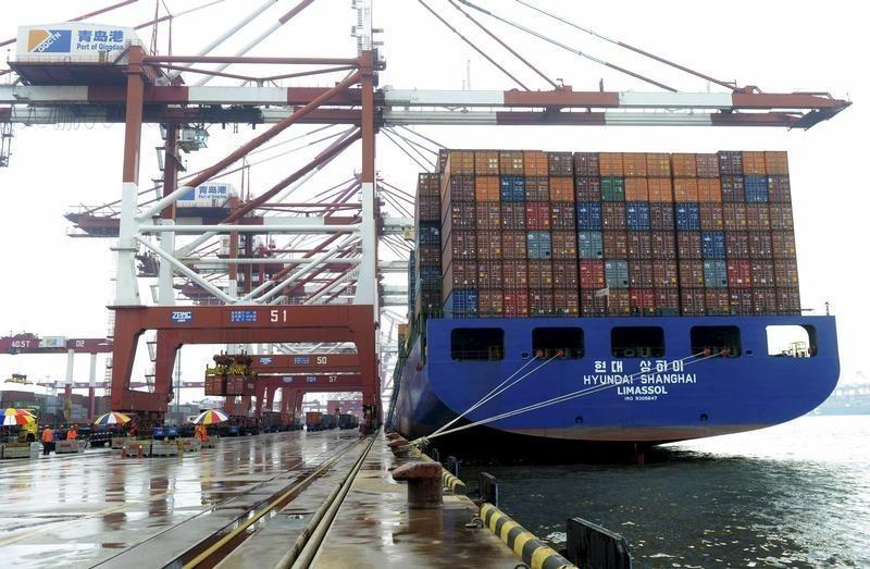 A cargo ship waits to be loaded with shipping containers at a port in Qingdao