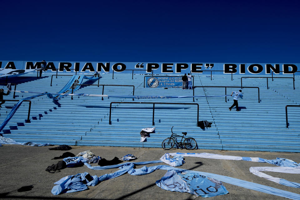 Temperley soccer fans hang banners in the empty stands of Alfredo Beranger Stadium before their team's match against Club Atletico Alvarado in Lomas de Zamora, Argentina, Friday, Aug. 27, 2021. Four hours before the match, soccer fans are allowed to enter and hang banners, and must remove them after the match. (AP Photo/Natacha Pisarenko)