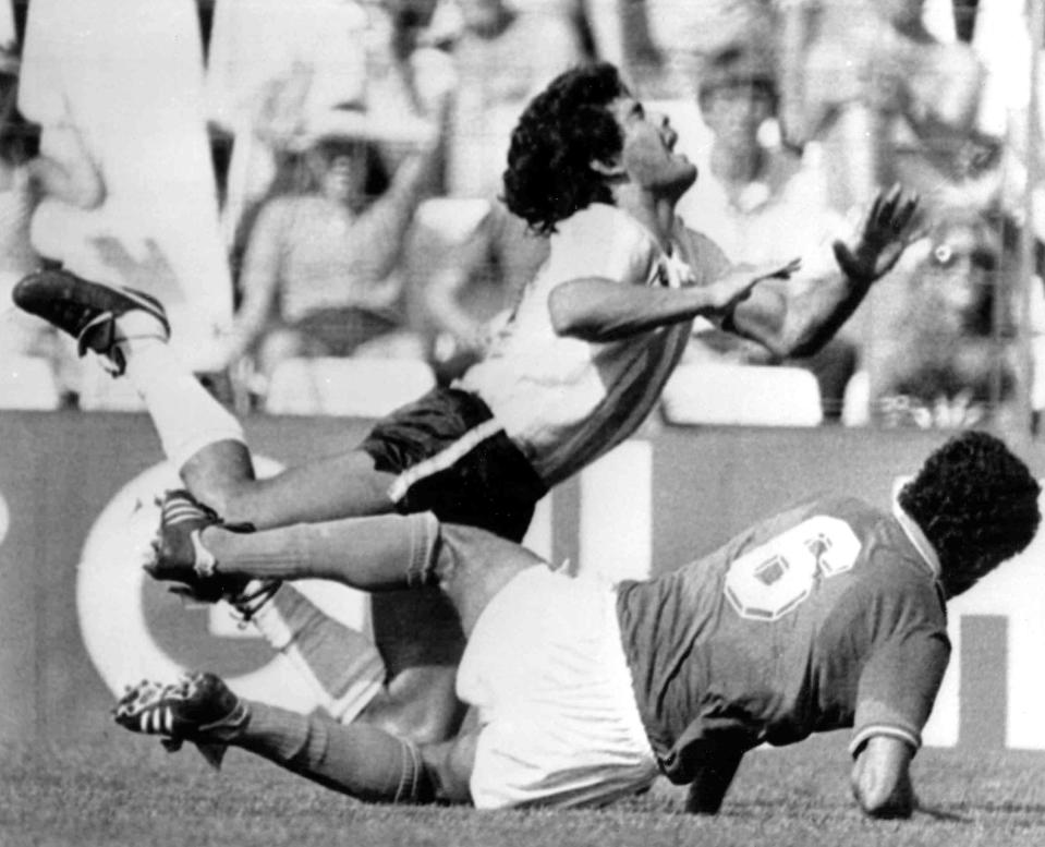 FILE - In this June 29, 1982 file photo, Diego Maradona is tackled by Italy's Claudio Gentile during a World Cup second-round match between Italy and Argentina at Sarra Stadium in Barcelona, Spain. The Argentine soccer great who was among the best players ever and who led his country to the 1986 World Cup title before later struggling with cocaine use and obesity, died from a heart attack on Wednesday, Nov. 25, 2020, at his home in Buenos Aires. He was 60. (AP Photo, File)