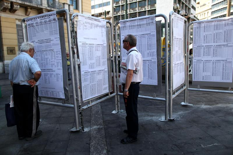 Greek men check lists with polling stations one day before general elections, in central Athens, on Saturday, June 16, 2012. Greeks cast their ballots this Sunday for the second time in six weeks, after May 6 elections left no party with enough seats in Parliament to form a government and coalition talks collapsed.(AP Photo/Petros Giannakouris)