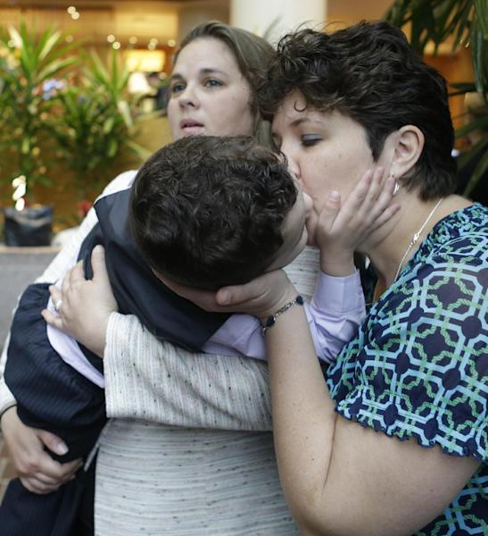 Nicole Yorksmith, right, kisses her three-year-old biological son while he is held by her spouse, Pam Yorksmith, during a news conference, Friday, April 4, 2014, in Cincinnati. Civil rights attorneys are arguing in Federal Court on Friday that a federal judge should prohibit Ohio officials from enforcing the state's ban on gay marriage. (AP Photo/Al Behrman)