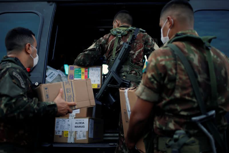 Members of the Brazilian Armed Forces load medical supplies to a military helicopter, amid the spread of the coronavirus disease (COVID-19), in Boa Vista
