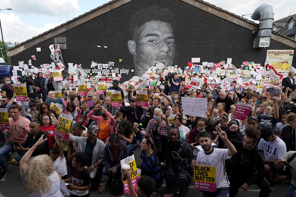 Hundreds of protesters take the knee at Marcus Rashford mural (PA)