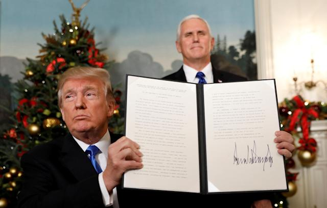 <p>Vice President Mike Pence stands behind as President Donald Trump holds up the proclamation he signed that the United States recognizes Jerusalem as the capital of Israel and will move its embassy there, during an address from the White House in Washington, Dec. 6, 2017. (Photo: Kevin Lamarque/Reuters) </p>