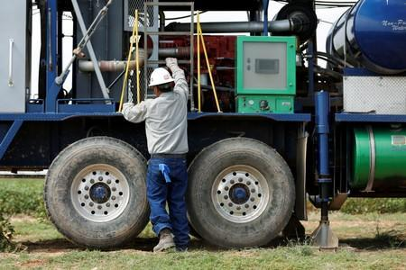 An oil field worker prepares a swabbing rig in a field in Seminole