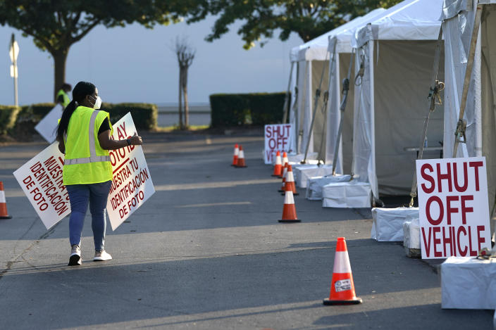 A healthcare worker puts out signs at a Texas Division of Emergency Management free COVID-19 testing site at Minute Maid Park Saturday, Aug. 8, 2020, in Houston. The newly opened mega site, which has eight drive-thru lanes and four walk-up lanes, has the ability to process 2,000 tests per day. (AP Photo/David J. Phillip)