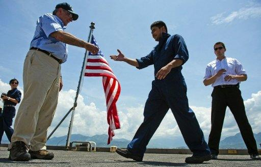US Secretary of Defense Leon Panetta (L) hands out coins to members of the crew as he visits the USNS Richard E. Byrd docked in Vietnam's Cam Ranh Bay on June 3. Panetta became the first Pentagon chief to visit southern Cam Ranh Bay since the end of the Vietnam War