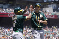 Oakland Athletics' Elvis Andrus, left, celebrates with Matt Olson after they scored on Matt Chapman's two-run single during the first inning of a baseball game against the San Francisco Giants in San Francisco, Sunday, June 27, 2021. (AP Photo/Jeff Chiu)
