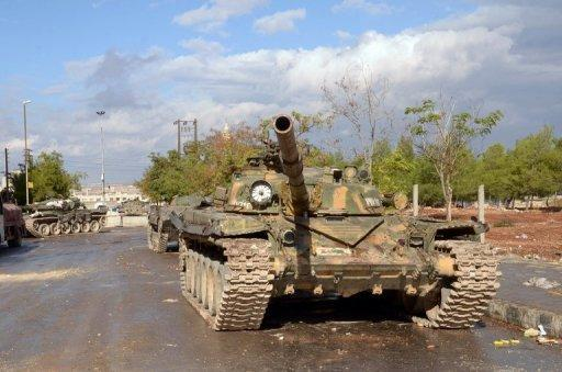 Syrian army tanks are seen stationed along a street in the northern province of Aleppo, on November 10. Syrian opposition groups meeting in Doha agreed in principle on Sunday on a plan to unite against President Bashar al-Assad following marathon talks and pressure from international backers