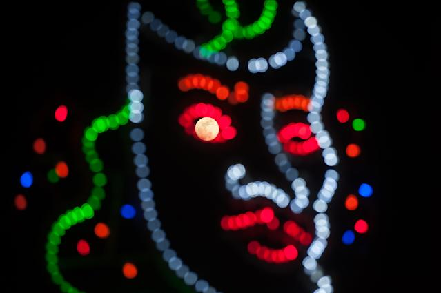 <p>A 'super moon' is seen on the sky trough a carnival lighting mask in Malaga, Spain, Jan. 30, 2018. (Photo: Jesus Merida/SOPA Images/LightRocket via Getty Images) </p>