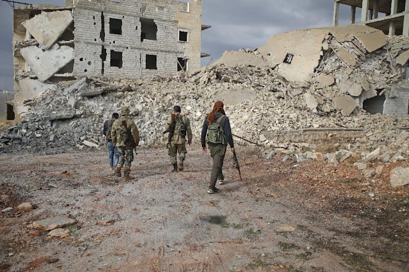 Syrian rebels from the National Liberation Front (NLF)walk through the Aleppo province's al-Rashidin district on November 26, 2018