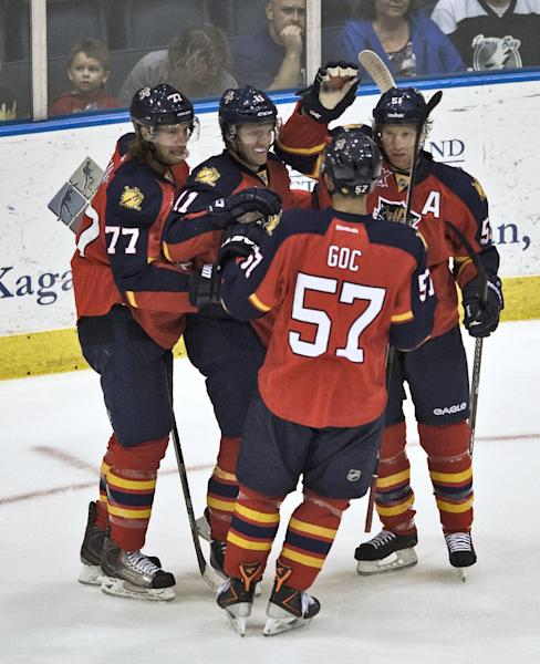 Florida Panthers' Tom Gilbert (77), Jonathan Huberdeau (11), Marcel Goc (57) and Brian Campbell, right, celebrate Huberdeau's goal against the Tampa Bay Lightning during the first period of an NHL preseason hockey game Thursday, Sept. 26, 2013, in Estero, Fla. (AP Photo/Steve Nesius)