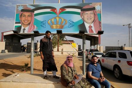 People sit next of a billboard with a picture of Jordan's King Abdullah and Crown Prince Hussein as they wait to travel to Syria at Jordan's Jaber border crossing, near Syria's Nassib checkpoint, near Mafraq, Jordan, October 25, 2018. Picture taken October 25, 2018. REUTERS/Muhammad Hamed