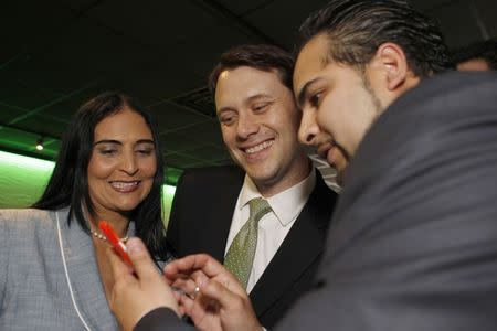 Georgia State Senator (D-Decatur), and gubernatorial candidate Jason Carter (C), checks out a cell phone picture with Pastor Blanca Domingez (L) and Antonio Molina after speaking at a private event in Tucker, Georgia May 23, 2014. REUTERS/Tami Chappell