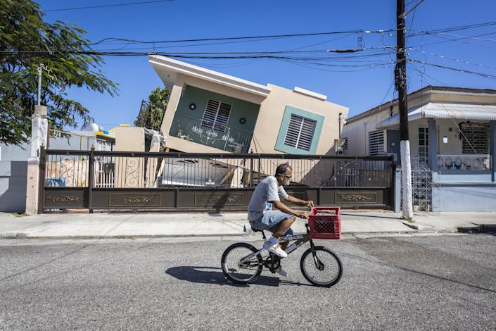 A man rides his bike in front of a collapsed house after a 6.4-magnitude earthquake hit Guanica, Puerto Rico, on Jan. 11, 2020. (Photo: Anadolu Agency via Getty Images)