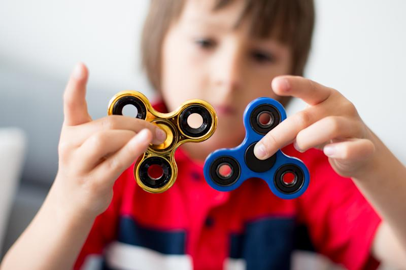 A boy plays with two spinners.