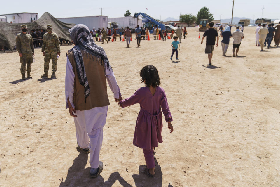 A man walks with a child through Fort Bliss' Doña Ana Village where Afghan refugees are being housed, in New Mexico, Friday, Sept. 10, 2021. The Biden administration provided the first public look inside the U.S. military base where Afghans airlifted out of Afghanistan are screened, amid questions about how the government is caring for the refugees and vetting them. (AP Photo/David Goldman)