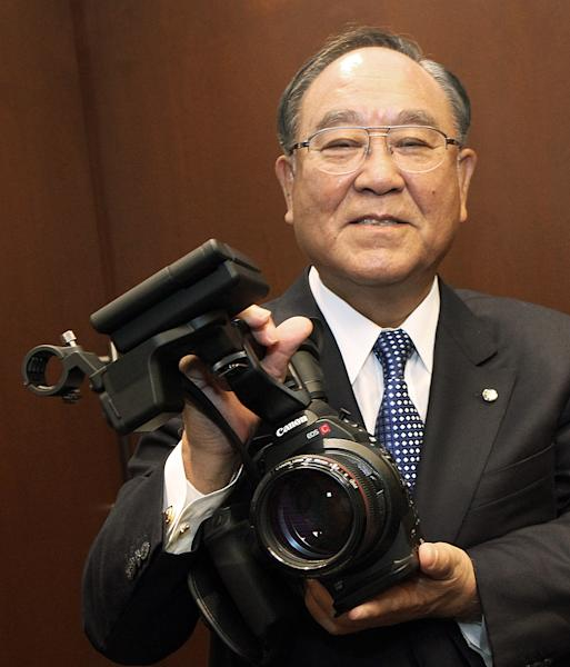 Fujio Mitarai, chairman and CEO of Canon, Inc., holds one in the line of new EOS C300 interchangeable-lens digital cinema cameras, at the introduction of the Cinema EOS System, Canon's all-new lineup of professional motion picture cameras and lenses, at Paramount Studios in Los Angeles Thursday, Nov. 3, 2011. The Cinema EOS offers compatibility with Canon's existing array of EF lenses used in digital single-lens reflex cameras, including the existing video-capable EOS 5D Mark II. (AP Photo/Reed Saxon)