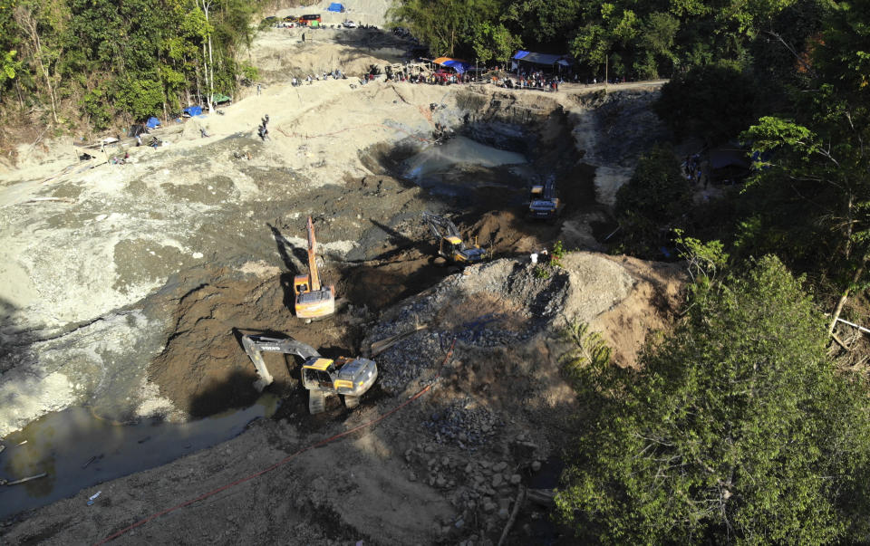 Rescuers use heavy machinery as they search for victims at a collapsed gold mine in Parigi Moutong, Central Sulawesi, Indonesia, Thursday, Feb. 25, 2021. The illegal gold mine in Central Indonesia collapsed on miners working inside, leaving a number of people killed, officials said Thursday. (AP Photo/M. Taufan)