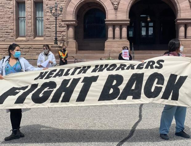 Health care workers hold a banner in the wind at a protest at Queen's Park on Sunday.