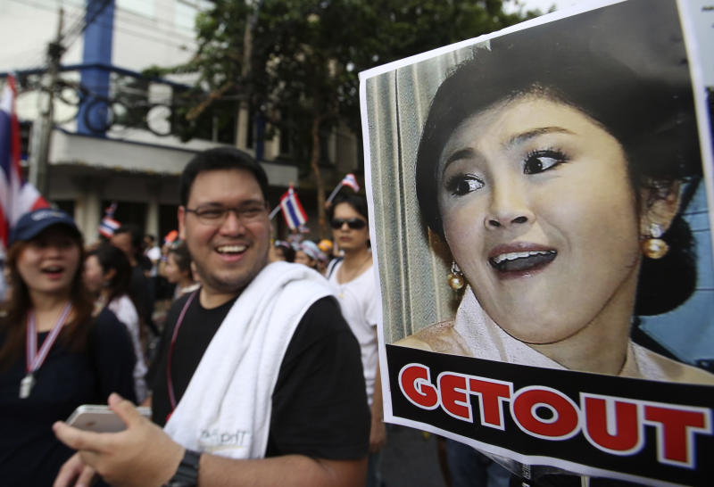 A poster of Thai Prime Minister Yingluck Shinawatra is displayed during a rally, protesting against an amnesty bill in Bangkok, Thailand, Monday, Nov. 11, 2013. Thailand's Senate convened a highly charged session Monday to determine the fate of the amnesty bill that could pave the way for the return of the country's divisive self-exiled former leader Thaksin Shinawatra, Yingluck's brother. Thousands of protesters rallied in several parts of Bangkok, raising concerns of renewed political violence after three years of relative calm. (AP Photo/Sakchai Lalit)