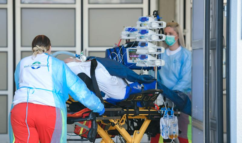 Medical staff wearing protective masks and clothing bring a patient to the emergency room at the St. Josef Hospital in Bochum, Germany. Source: Getty