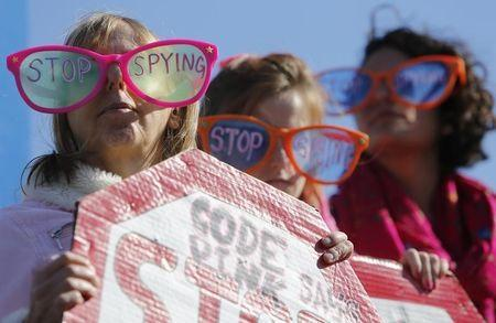"Demonstrators from the organization Code Pink wear toy glasses reading ""Stop Spying"" at the ""Stop Watching Us: A Rally Against Mass Surveillance"" near the U.S. Capitol in Washington, October 26, 2013. REUTERS/Jonathan Ernst"