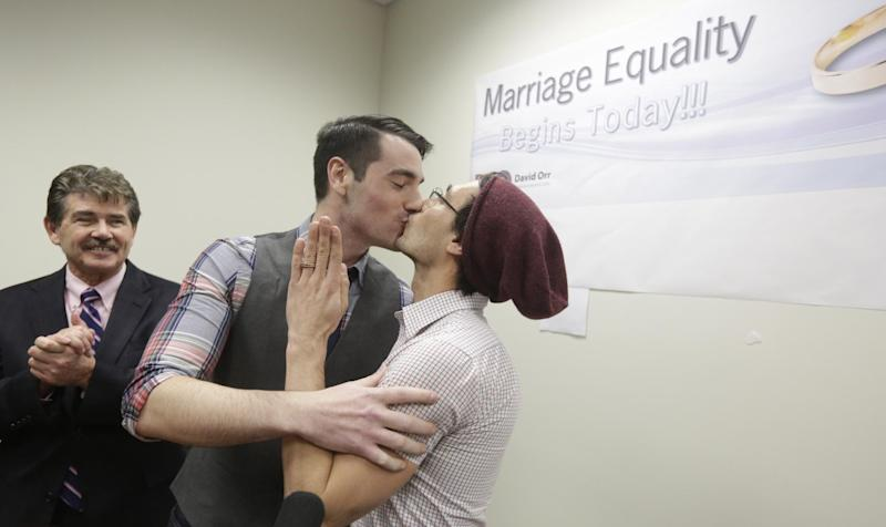 CORRECTS SPELLING TO WILK IN SECOND REFERENCE INSTEAD OF WILL - Charlie Gurion, center, and David Wilk kiss after obtaining their marriage license as Cook County Clerk David Orr, left,looks on Friday, Feb. 21, 2014, in Chicago. Same-sex couples in Illinois' largest county began receiving marriage licenses immediately after a federal judge's ruling Friday that some attorneys said could give county clerks statewide justification to also issue the documents right away. Illinois approved same-sex marriage last year; the new law takes effect June 1. However, U.S. District Judge Sharon Johnson Coleman ruled Friday that same-sex marriages can begin now in Cook County, where Chicago is located. Gurion and Wilk were the first couple to show up to get a license after the judge made her ruling. (AP Photo/M. Spencer Green)
