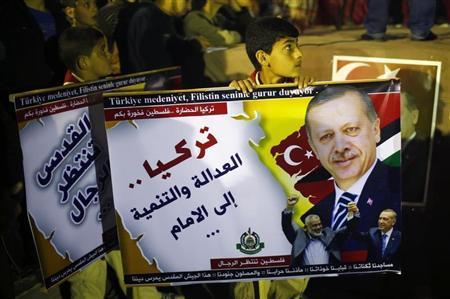 A Palestinian boy holds a poster of Turkish Prime Minister Tayyip Erdogan as he celebrates after Erdogan declared victory in local polls during a rally organised by Hamas movement in the northern Gaza Strip March 31, 2014. REUTERS/Mohammed Salem