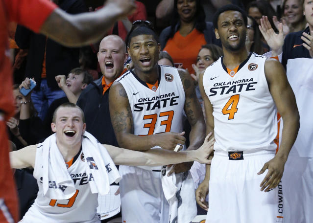 Oklahoma State guard Phil Forte (13), guard Marcus Smart (33) and wing Brian Williams (4) cheer on the bench following a dunk by teammate Le'Bryan Nash in the second half of an NCAA college basketball game against Texas Tech in Stillwater, Okla., Saturday, Feb. 22, 2014. Oklahoma State won 84-62. (AP Photo/Sue Ogrocki)
